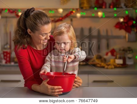 Happy Mother And Baby Whisking Dough In Christmas Decorated Kitc