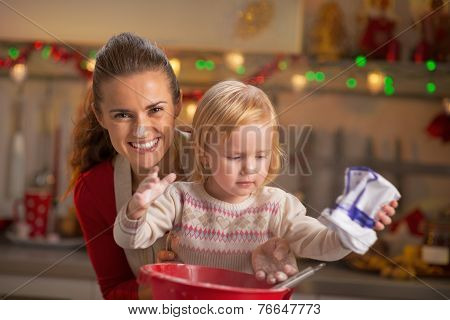Portrait Of Flour Smeared Mother And Baby Making Christmas Cooki