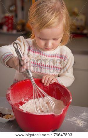 Baby Whisking Flour In Kitchen