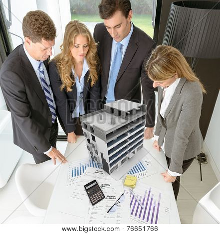 Meeting with people around a table with an architectural model on top of documents and charts