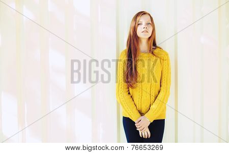 Portrait of a young naughty redhead woman in yellow sweater against an urban texture background