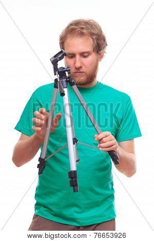 Man Unfolding A Tripod