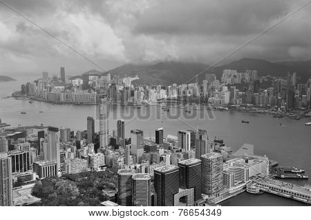 Victoria Harbor aerial view and skyline in Hong Kong with urban skyscrapers in black and white.