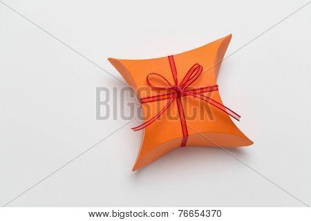 Orange gift box with decorative red ribbon