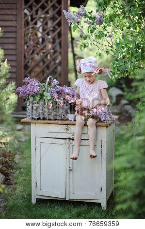 cute happy little girl making lilacs flower wreath in sunny spring garden