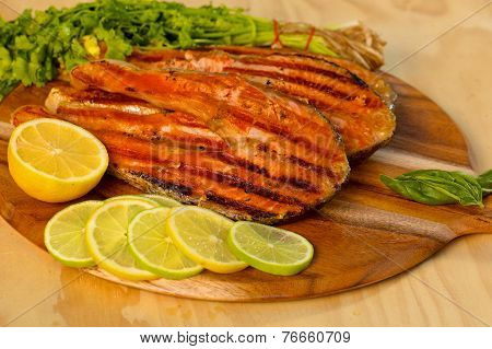 Grilled salmon fillet with lime and parsley on a wooden board