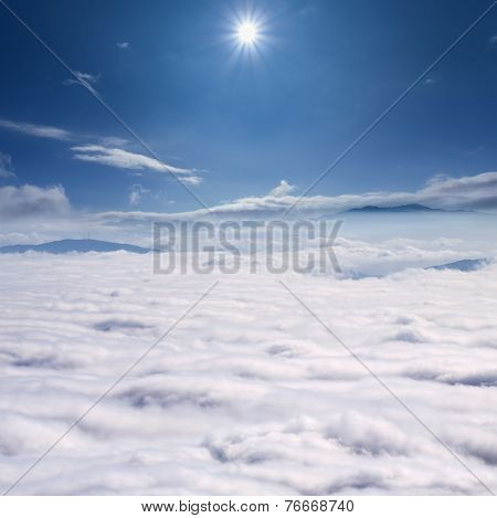 Peaks Above The Clouds Against Sun