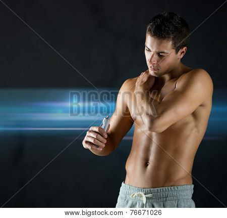 sport, bodybuilding, medicine and people concept - young man applying pain relief gel on his shoulder over dark background