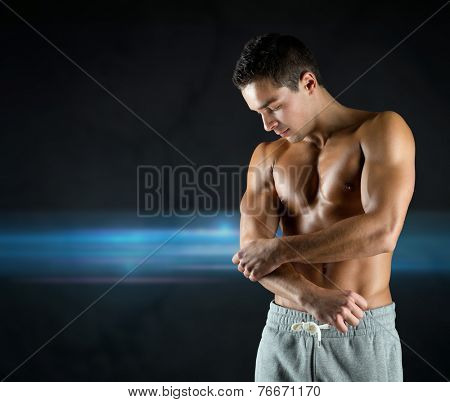 pain, sport, bodybuilding, health and people concept - young male bodybuilder touching injured elbow over dark background