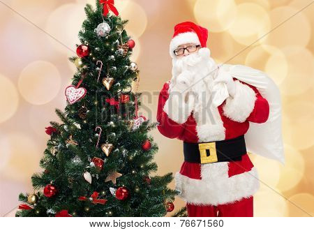 christmas, holidays and people concept - man in costume of santa claus with bag and christmas tree making hush gesture over beige lights background