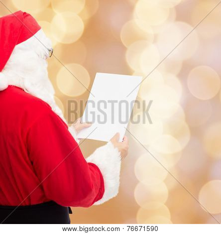 christmas, holidays and people concept - man in costume of santa claus reading letter over beige lights background