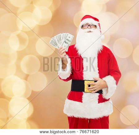 christmas, holidays, winning, currency and people concept - man in costume of santa claus with dollar money over beige lights background