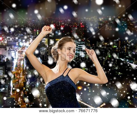 people, party, holidays and christmas concept - smiling woman dancing with raised hands over snowy night city background