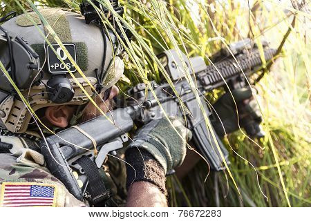 American Soldier Aiming His Rifle On The Grass
