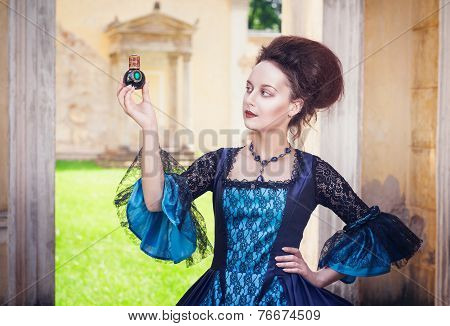 Beautiful Woman In Medieval Dress With Perfume Bottle