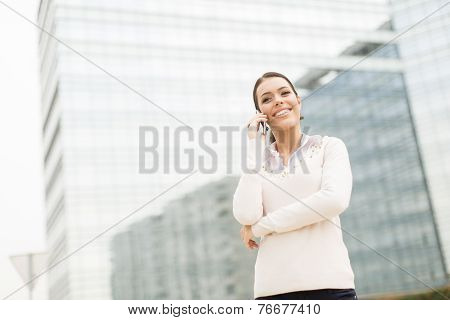 Young Business Woman Talking On Mobile Phone In Front Of Office Building