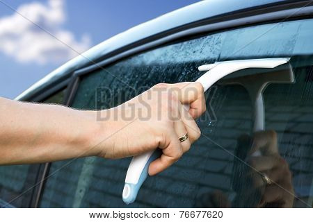 Worker Washing The Car Window With A Scraper