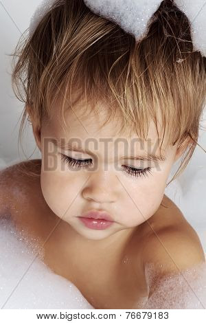 Little girl surrounded soap suds.