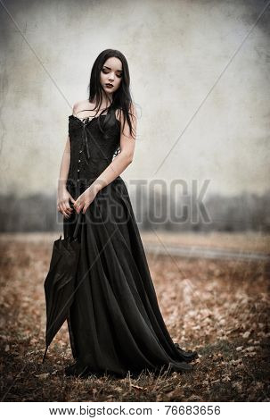 Beautiful Sad Goth Girl Holds Black Umbrella. Grunge Texture Effect