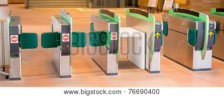 Turnstiles In Underground Railway Station. Green Arrows Pointing To The Way Forwards. Green Barriers