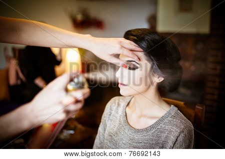 Beautiful bride doing her hair and makeup. Hairstylist spraying hairspray on her updo