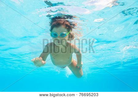 Small boy with goggles swims alone under water