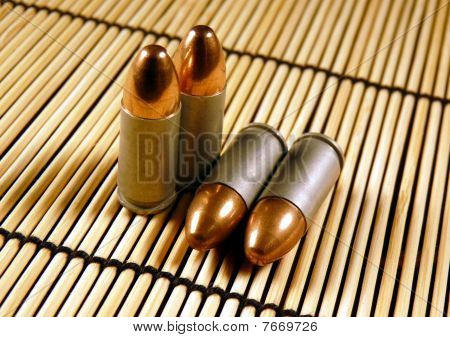 Full metal jacket 9mm Handgun bullets on a bamboo mat
