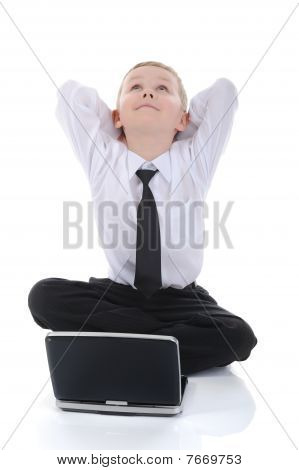 Little Boy With A Laptop Sitting On The Floor.