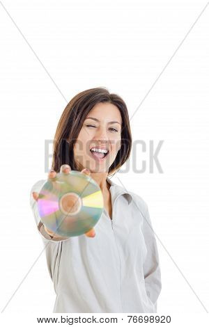 Casual Smiling Woman Holding Up Compact Disc Or Cd  And Looking At Camera And Winks