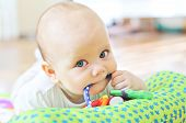 pic of love bite  - baby laying  with a toy in mouth - JPG