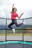 picture of 11 year old  - 12 year old teenage girl jumping on a trampoline in the Andorra Pyrenees Mountains - JPG