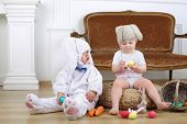 picture of bunny costume  - Little boy in costumes bunny and girl in knitted hat with hare ears sitting on floor with Easter eggs - JPG