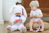 pic of bunny costume  - Little boy and girl in costumes bunny sitting on floor with Easter eggs - JPG