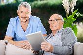 picture of male nurses  - Portrait of smiling male caretaker and senior man holding digital tablet at nursing home porch - JPG