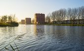 image of highrises  - Highrise along a river at sunset in autumn - JPG