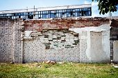 image of old stone fence  - Abandoned factory behind old brick fence on a sunny day - JPG