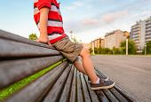 stock photo of short legs  - Closeup of boy legs with short pants sitting on the top of wooden bench park relaxing in a bored summer day - JPG