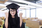 picture of graduation gown  - Woman in graduation gown expressing success in the class - JPG