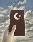 stock photo of islamic religious holy book  - Religious islamic concept photo collage showing a hand holding a islamic book against cloudy sky background - JPG