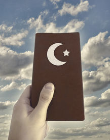 picture of islamic religious holy book  - Religious islamic concept photo collage showing a hand holding a islamic book against cloudy sky background - JPG