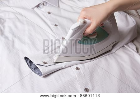 Modern Iron In Female Hand Ironing Sleeve Of Cotton Shirt