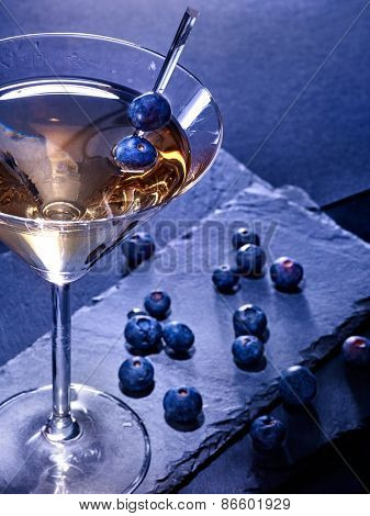 Blueberry gold drink on black background. Berries scattered