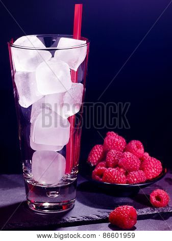 Red raspberry drink on black background. Empty glass with ice cube .
