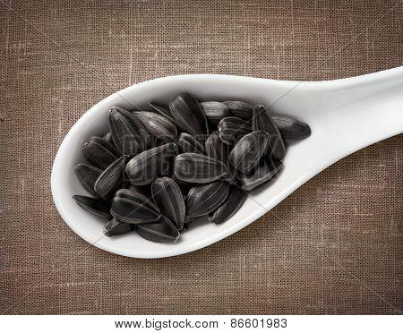 Black Sunflower Seeds In White Porcelain Spoon / High-res Photo Of Grain In White Porcelain Spoon On