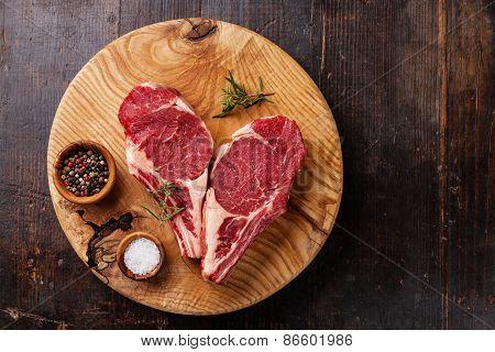 Raw Fresh Meat Ribeye Steak With Rosemary, Pepper And Salt On Dark Wooden Background