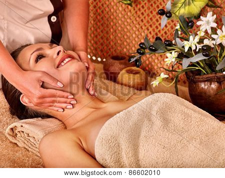 Woman getting head massage in tropical beauty spa. A lot of flower.