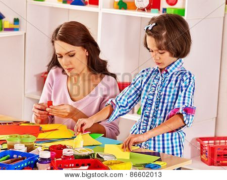 Child with woman  cutting out scissors paper in preschool.