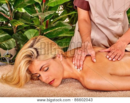 Blond woman getting massage in tropical spa. Visible hand masseuse.
