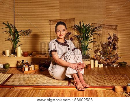 Bamboo massage at spa and woman. Sitting on floor.