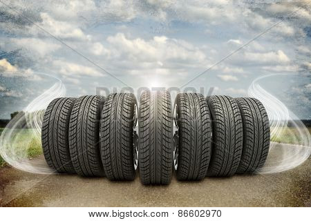 Wedge of new car wheels on old road with abstract smoke